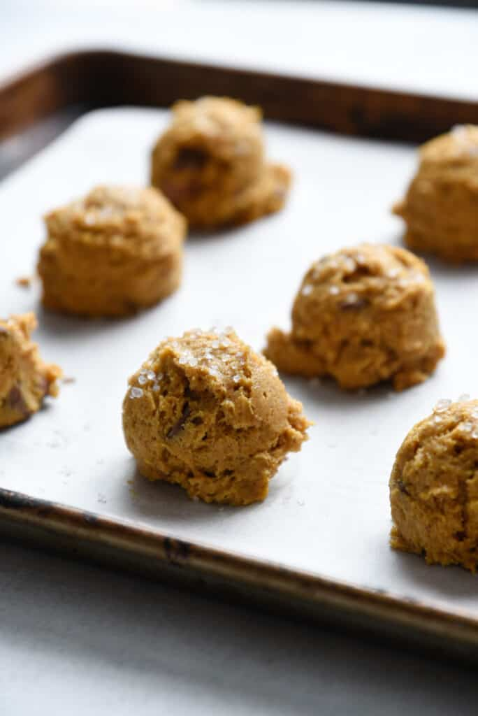 scoops of pumpkin chocolate chip cookie dough on a baking sheet