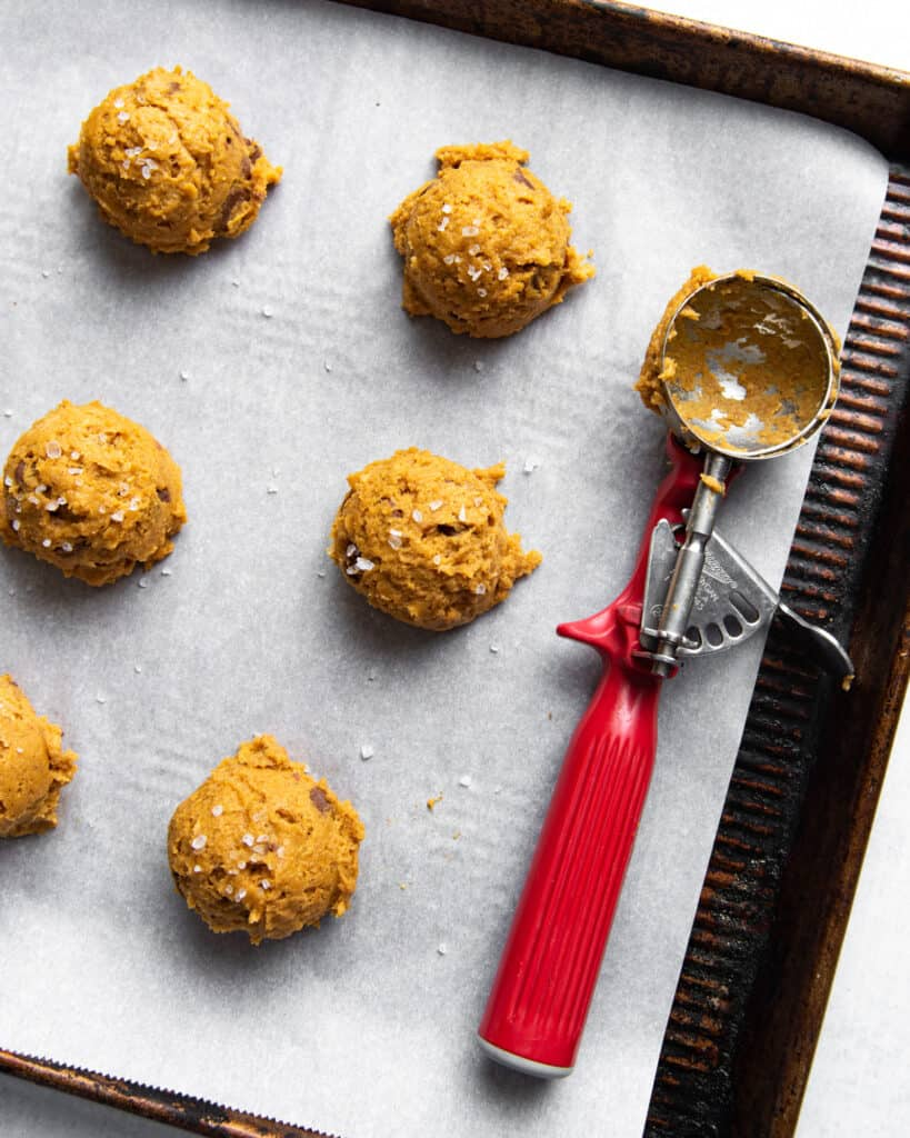 pumpkin chocolate chip cookie dough scooped onto a baking sheet next to a scoop