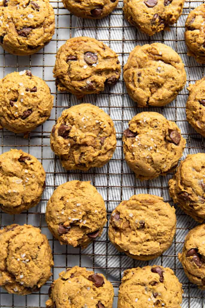 soft baked chocolate chip pumpkin cookies on a cooling rack fresh out of the oven