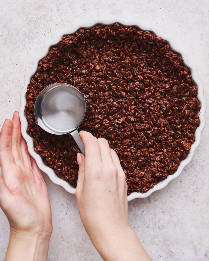 A chocolate rice Krispie crust being pressed into a pie plate with the back of a measuring cup